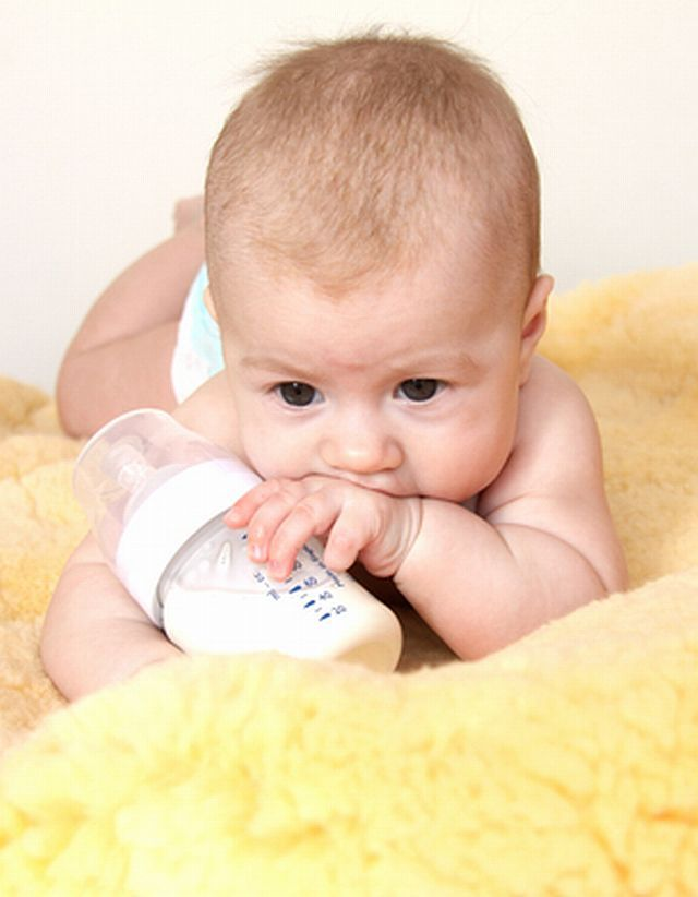 Cute baby with bottle of milk