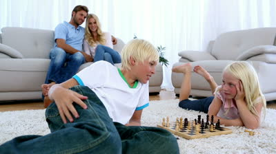 stock-footage-parents-watching-their-children-play-chess-on-rug-of-living-room